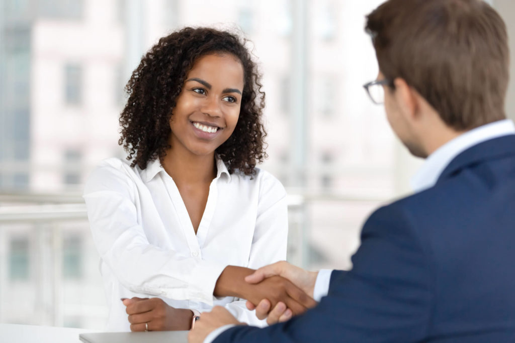 woman shakes man's hand in a professional setting
